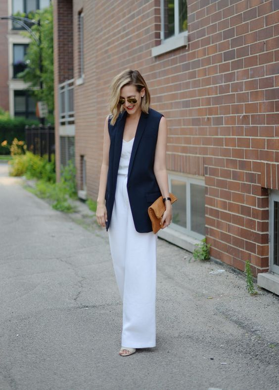a white strapless jumpsuit with wide leg pants, a navy long vest and a mustard clutch