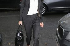 07 Amal Clooney rocking a thin striped black suit, a white top, grey shoes and a black bag