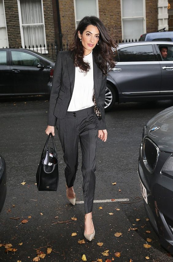 Amal Clooney rocking a thin striped black suit, a white top, grey shoes and a black bag