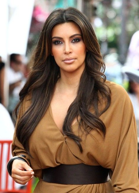 Kim Kardashian wearing long brown cascading hair with highlights to give it more dimension