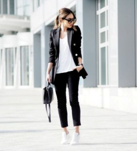 a black pantsuit with cropped pants, a white top, white sneakers and a black bag for a casual feel