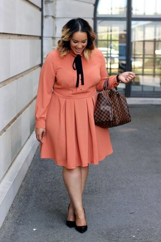 a coral knee shirtdress with long sleeves, black heels and a brown bag for a professional plus size look