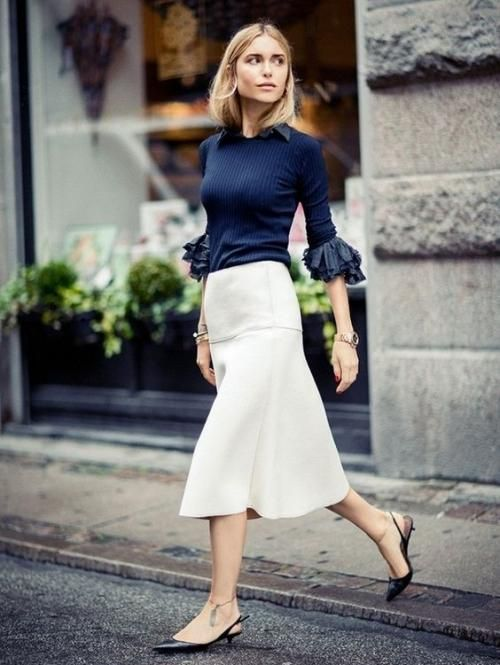 a navy blouse with ruffled sleeves, a creamy midi skirt with an A-silhouette and black kitten heels