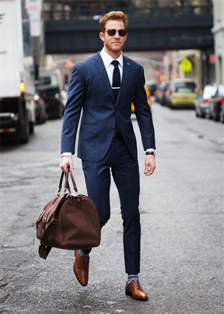 a navy suit, a white shirt, a black tie, brown shoes and striped socks