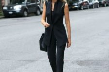 07 black pants, a top, a long fitting vest, black lace up shoes and a black bag