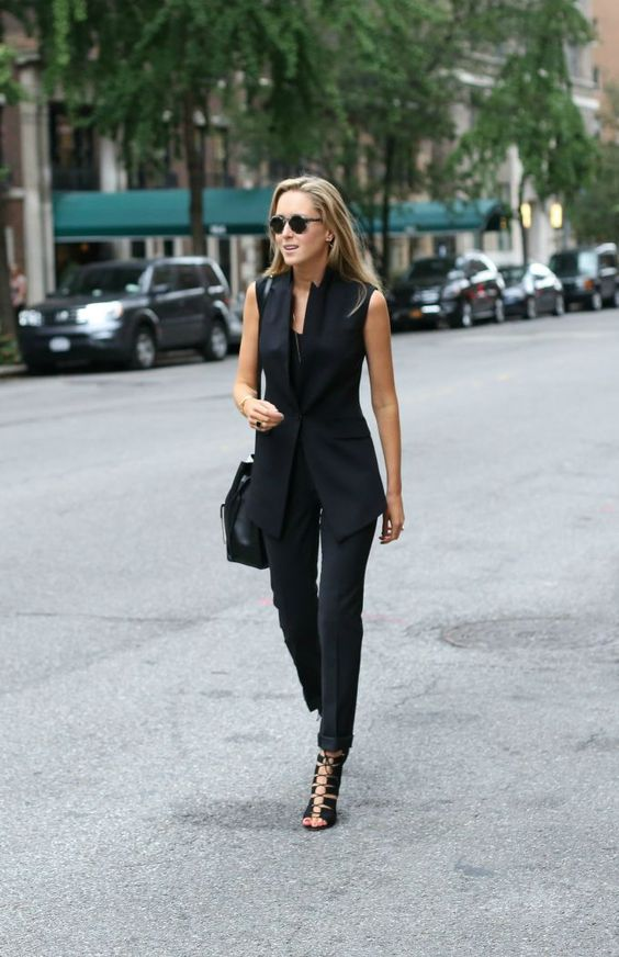 black pants, a top, a long fitting vest, black lace up shoes and a black bag