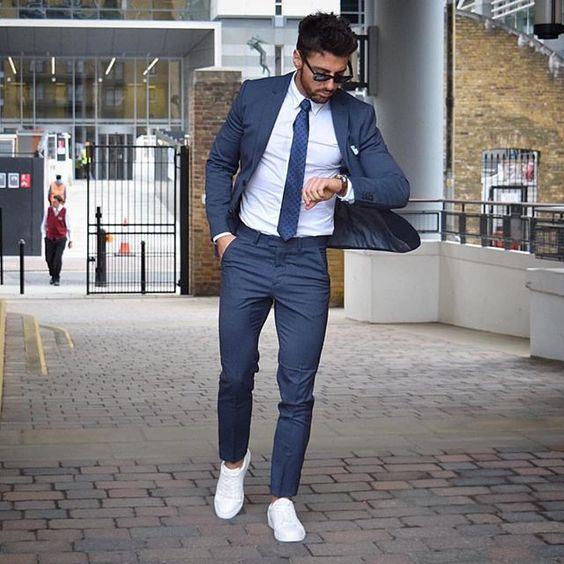 a slate grey suit, a matching tie, a white shirt and white sneakers for a fresh touch