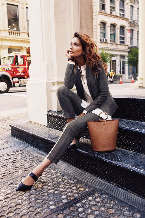 a grey checked pantsuit, a white button down, black strappy shoes and a creative bag
