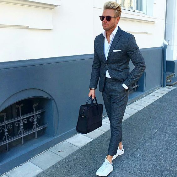 a grey suit, a white shirt, white sneakers and a black bag for a relaxed graduation look
