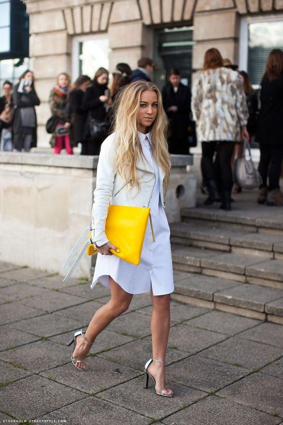 a white shirtdress, a white leather jacket, silver shoes and a lemon yellow large clutch