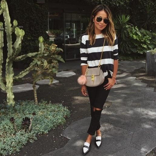 black ripped skinnies, a black and white striped top with short sleeves, black and whiet flats