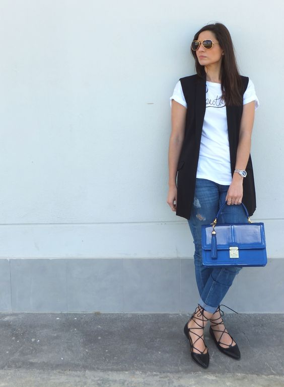 blue distressed jeans, a white tee, a black vest and black lace up shoes plus a blue bag