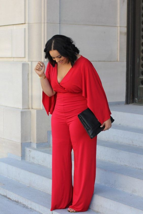 a gorgeous red jumpsuit with wide sleeves, a deep V neckline and wide pants to show off all the curves