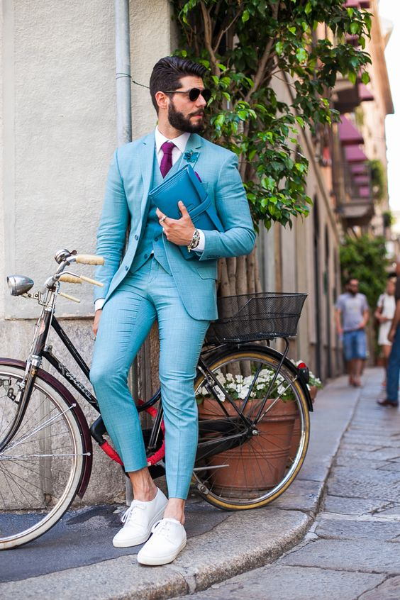 a turquoise three piece suit, a plum colored tie and white sneakers for a different look