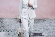 10 a white thin stripe pantsuit with a black top underneath, a neutral bag and red kitten heels