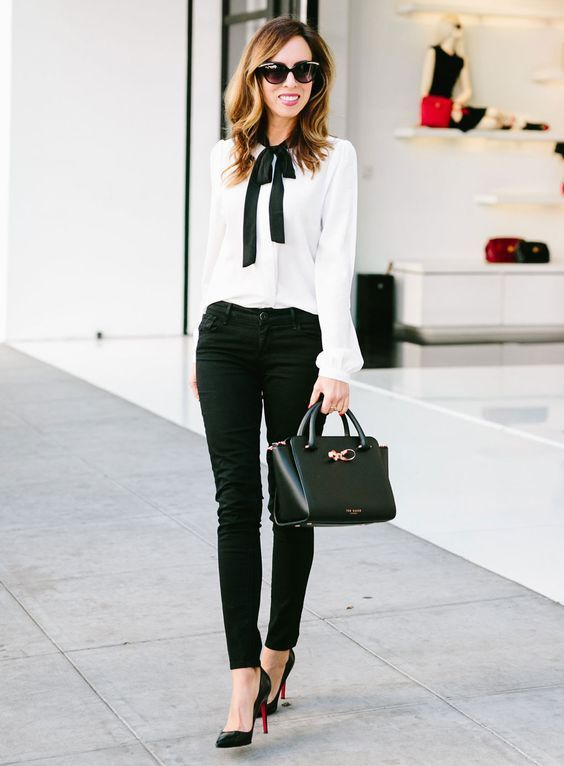 black jeans, a white blouse with a black bow, black heels and a comfy bag