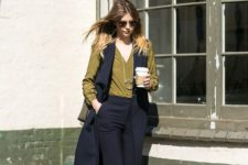 11 black cropped pants, a black long vest, an olive green shirt, white shoes for a professional look