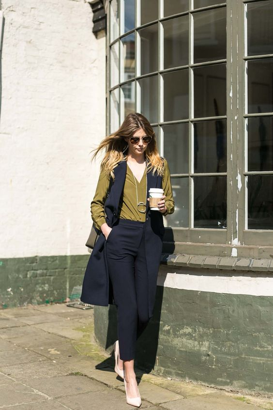 black cropped pants, a black long vest, an olive green shirt, white shoes for a professional look