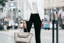 11 black jeans, a white top, a white jacket, nude shoes and a grey bag that spruce up the monochrome