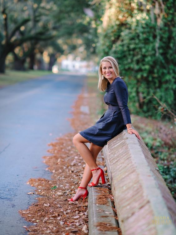 a navy fitting dress with long sleeves and red heels for a contrast