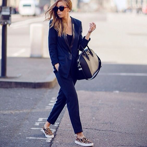 a navy suit, a black top, leopard print slipons and a black bag for a creative job