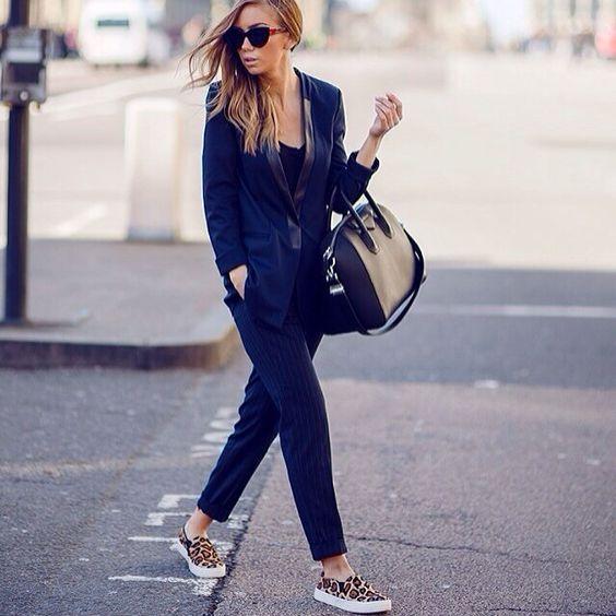 a navy suit, a black top, leopard print slipons and a black bag for a creative job