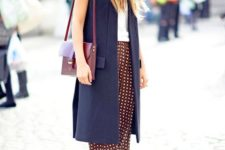 12 a white top, printed culottes, navy shoes, a navy long vest and a plum-colored bag