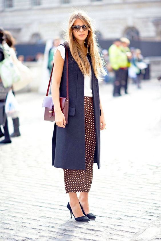 a white top, printed culottes, navy shoes, a navy long vest and a plum-colored bag
