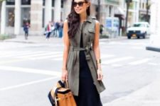 13 a black midi sleeveless dress, an olive green long vest and a tan colored bag