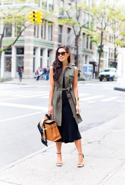 a black midi sleeveless dress, an olive green long vest and a tan colored bag