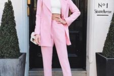 13 a pink suit, a white crop top, white shoes and a small white bag for a fashionable look