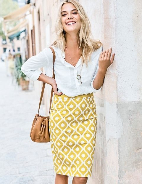 a white button down, a yellow printed pencil skirt, a tan bag