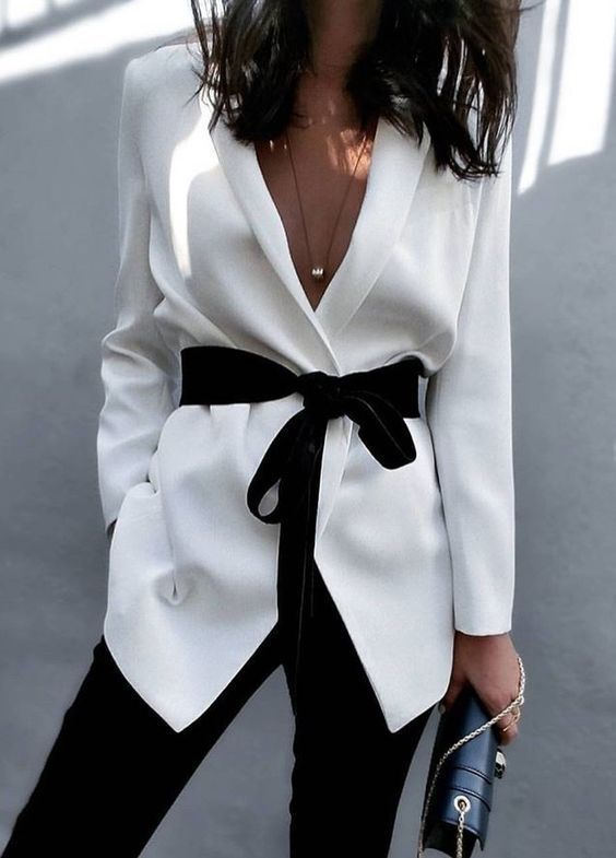 black pants, a white blazer with a black velvet sash with a bow for a creative office look