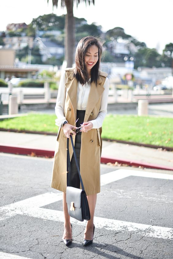 a black leather skirt, a white shirt, a tan long vest and black shoes for a girlish touch