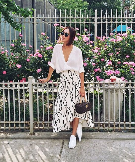 a printed high low midi skirt, a white button down, white sneakers and a small bag to rock