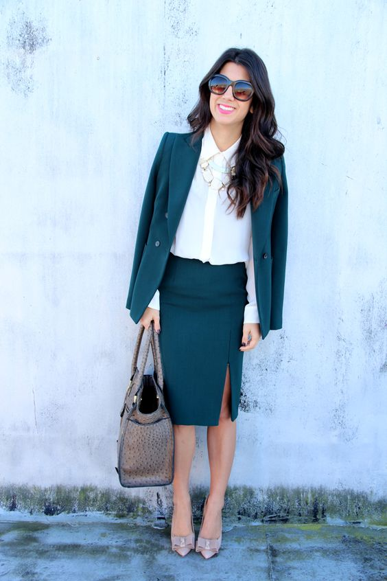 a teal suit with a skirt and a slit, a cream button down, a statement necklace, blush shoes