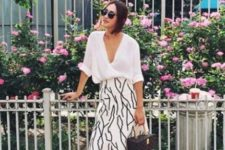 14 a white button down with cuffed sleeves, a printed midi skirt, whiet sneakers and a catchy bag