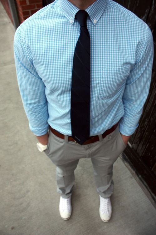 grey pants, a blue gingham shirt, a black striped tie and white sneakers