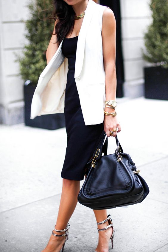 a black sleeveless midi dress, a creamy long vest, strappy heels and a large bag