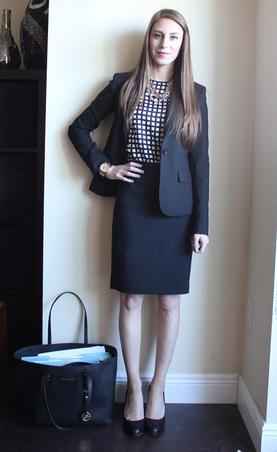a black suit with a knee skirt, a windowpane print top, black shoes and a bag