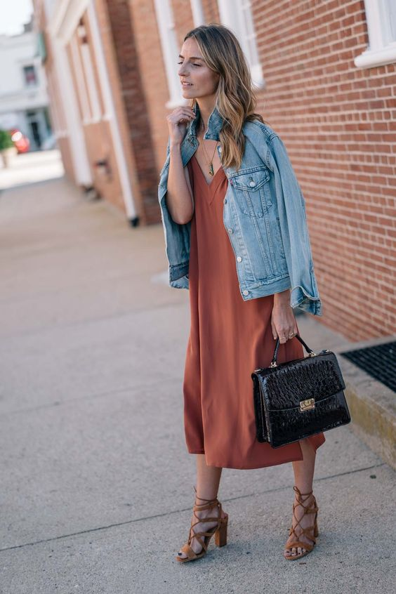 a rust colored slip dress, a denim jacket, tan strappy heels and a black bag