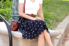 16 a white t-shirt, a navy polka dot skirt, brown flats and a matching bag for a retro-inspired look