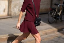 16 black slipons and a burgundy suit of a skirt and a top plus a black bag for a non-boring look