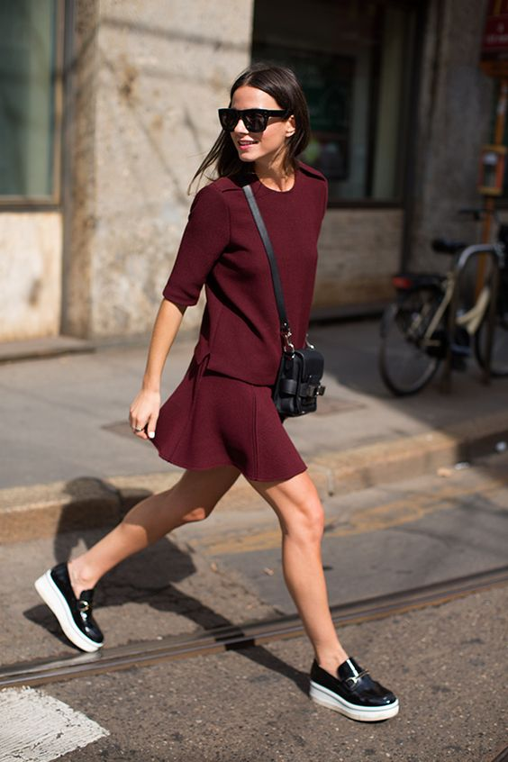 black slipons and a burgundy suit of a skirt and a top plus a black bag for a non boring look