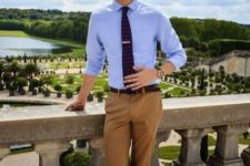 16 tan pants, a blue shirt, a striped tie and moccasins with no socks plus sunglasses