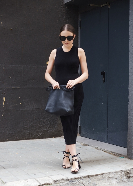 With black midi dress, sunglasses and black leather bag