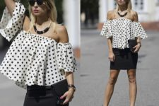 With black mini skirt, black clutch and black and beige sandals