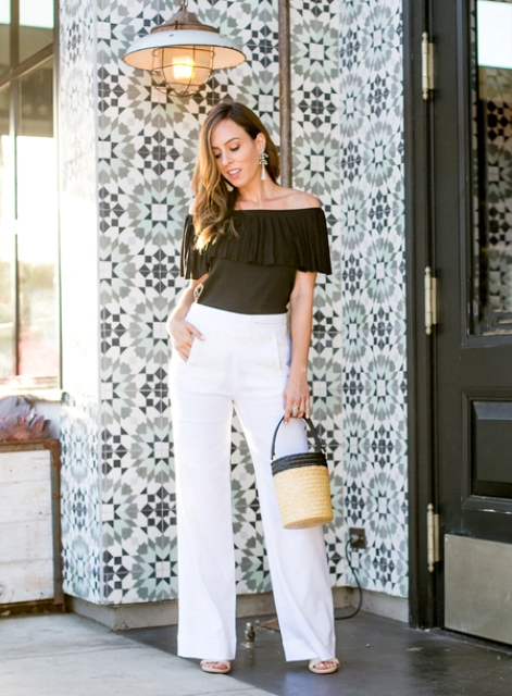 With black off the shoulder top, white wide leg pants and heels