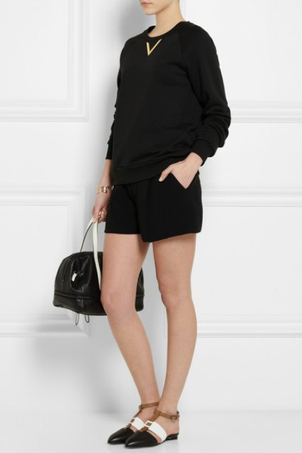 With black shirt, black shorts and bag
