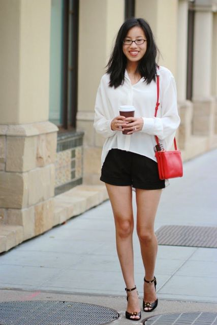 With black shorts, ankle strap shoes and red bag
